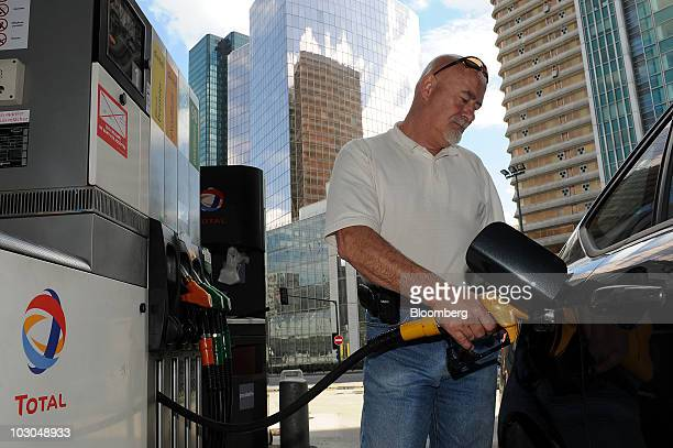 William Shapman fills his car with fuel at a Total SA gas station in Paris France on Thursday July 22 2010 The company Europe's biggest oil refiner...