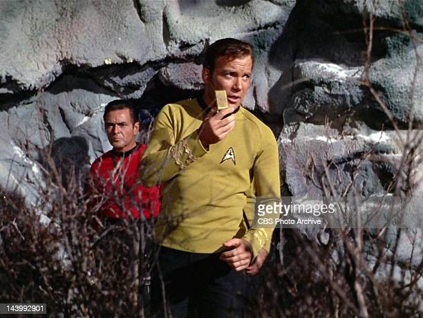 """William Shatner as Captain James T. Kirk speaking into his communicator with James Doohan as Montgomery """"Scotty"""" Scott in the background in the STAR..."""