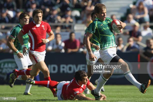 William SmallSmith of South Africa skips a tackle from Will Price of Wales to score a try during the Plate Semi Final match between South Africa and...