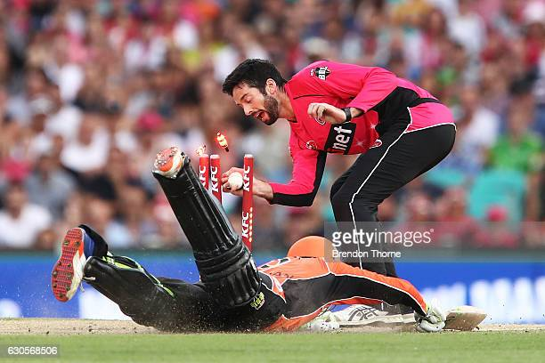 William Somerville of the Sixers attempts to run out Sam Whiteman of the Scorchers during the Big Bash League match between the Sydney Sixers and...