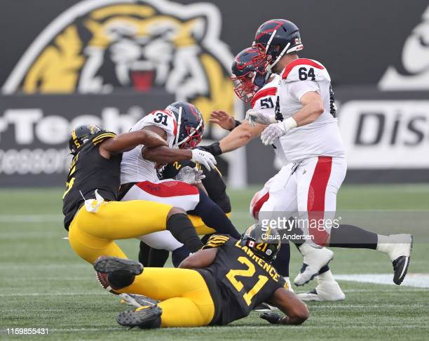 William Stanback of the Montreal Alouettes is tackled by Adrian Tracy of the Hamilton Tiger-Cats during a CFL game at Tim Hortons Field on June 28,...