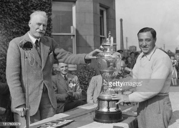 William Turnesa of the United States is presented with the Championship Trophy by Patrick Bowes-Lyon,15th Earl of Strathmore and Kinghorne after...