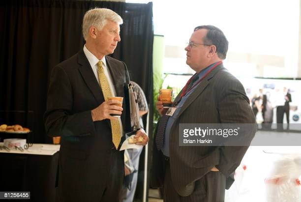 William W George a director on the ExxonMobil board talks with Brian Flannery before the ExxonMobil annual shareholders meeting at the Morton H...