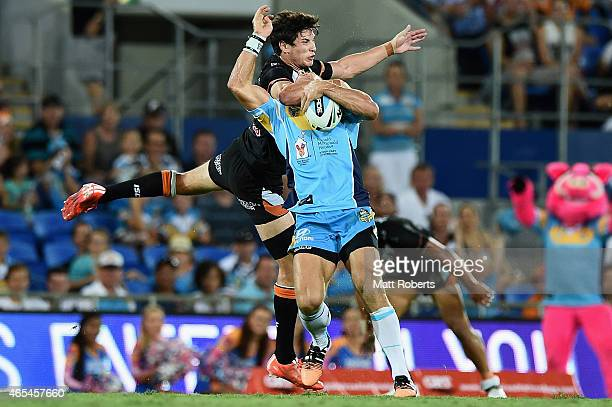 William Zillman of the Titans is tackled high by Mitchell Moses of the Tigers during the round one NRL match between the Gold Coast Titans and the...