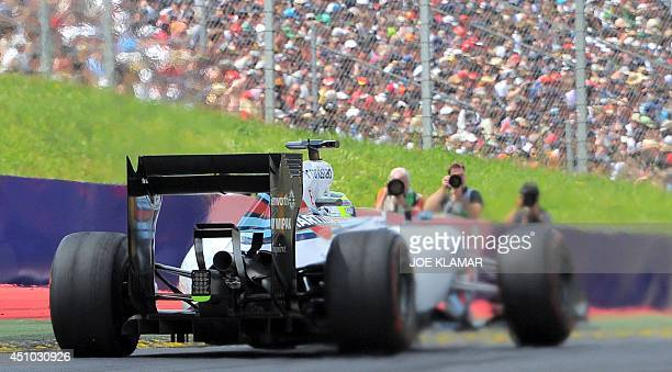 Williams' Brazilian driver Felipe Massa passes by photographers as he competes in the Austrian Formula One Grand Prix at the Red Bull Ring in...