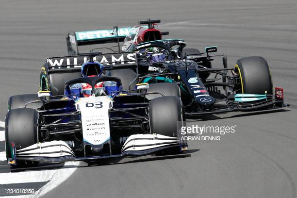 Williams' British driver George Russell and Mercedes' British driver Lewis Hamilton drives at Becketts Corner during the practice 1 session of the...