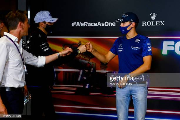 Williams' British driver George Russell fist bumps with Alpine's French driver Esteban Ocon during a press conference at the Circuit de Catalunya on...