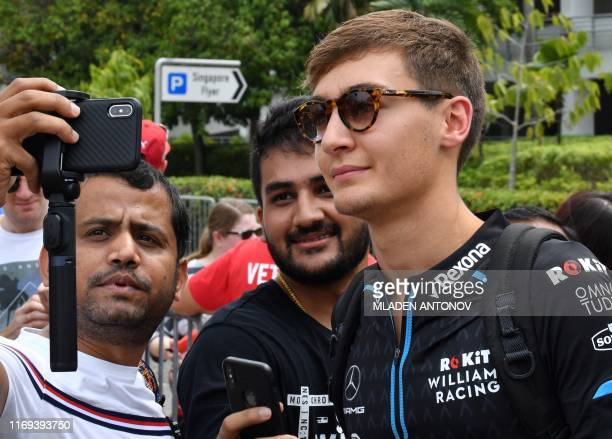Williams' British driver George Russell poses for a photo with fans before entering the paddock of the Formula One Singapore Grand Prix night race in...