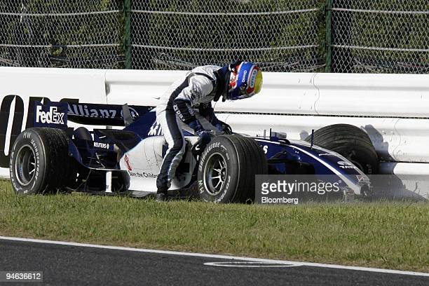 Williams driver Mark Webber extricates himself from his damaged car following a crash during the Formula 1Grand Prix of Japan in Suzuka, on Sunday,...