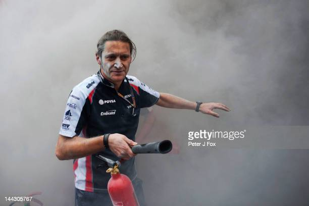 Williams mechanic helps fight the fire that broke out at the back of their team garage after they celebrated winning the Spanish Formula One Grand...