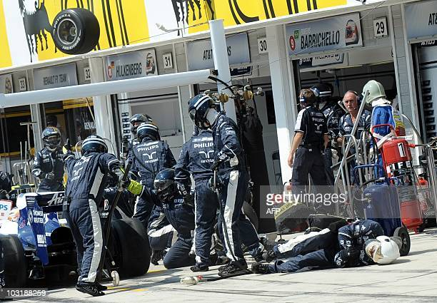A williams mechanics lies down after being hit by a wheel of Mercedes GP's German driver Nico Rosberg in the pits of the Hungaroring circuit on...