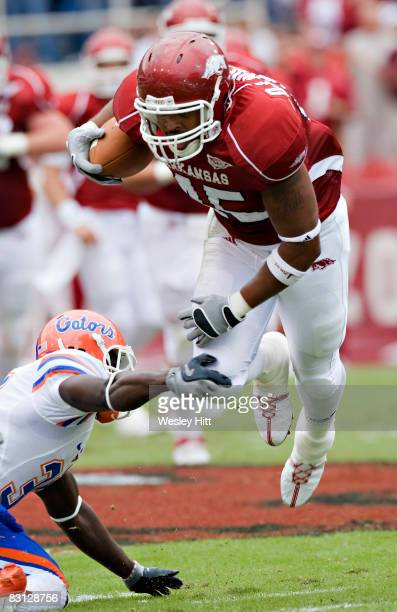 J Williams of the Arkansas Razorbacks is tripped up by a defender during a game against the Florida Gators at Donald W Reynolds Stadium on October 4...