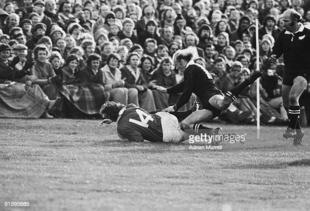 Williams of the British Lions dives past New Zealand's Grant Batty to score the only try of the match between New Zealand and the British Lions on...
