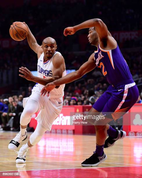 J Williams of the LA Clippers drives on TJ Warren of the Phoenix Suns during the first half at Staples Center on December 20 2017 in Los Angeles...