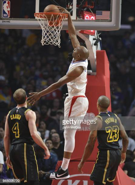 J Williams of the LA Clippers gets past Alex Caruso of the Los Angeles Lakers and Gary Payton II of the Los Angeles Lakers for a dunk in the first...