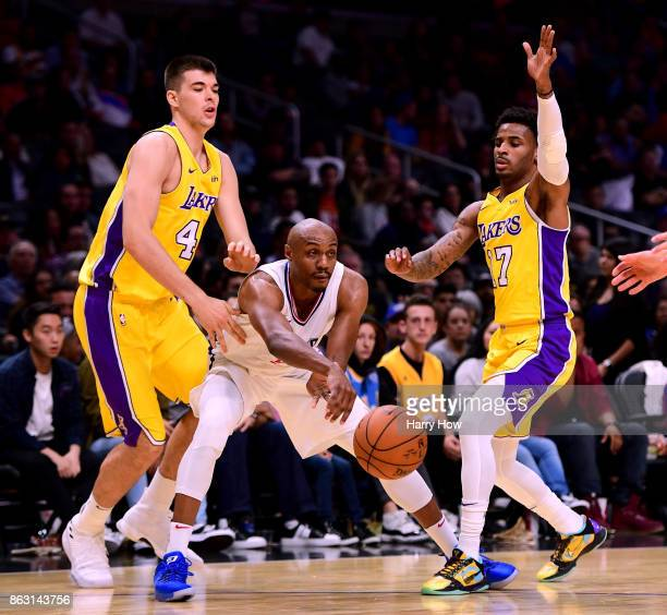 J Williams of the LA Clippers passes between the defense of Ivica Zubac and Vander Blue of the Los Angeles Lakers at Staples Center on October 10...