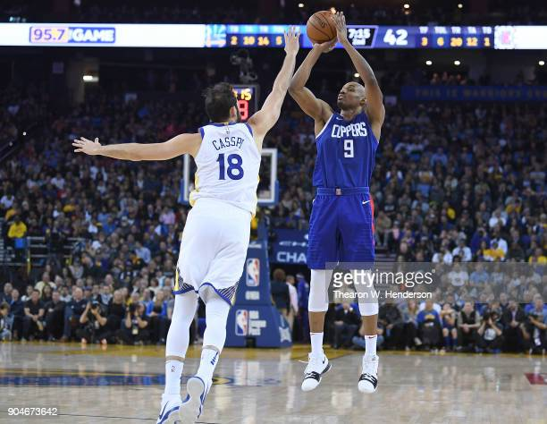 J Williams of the LA Clippers shoots over Omri Casspi of the Golden State Warriors during the first half of their NBA Basketball game at ORACLE Arena...