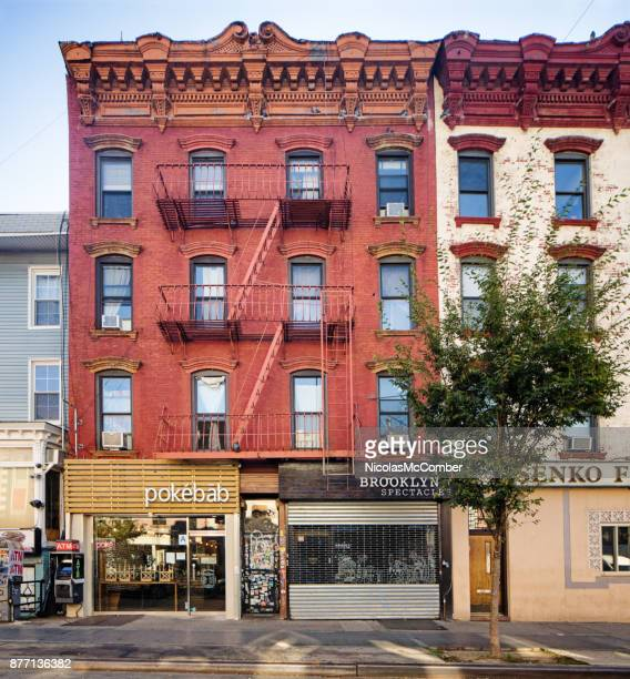 williamsburg brooklyn apartment buildings with street level restaurants and shops - brooklyn new york stock photos and pictures