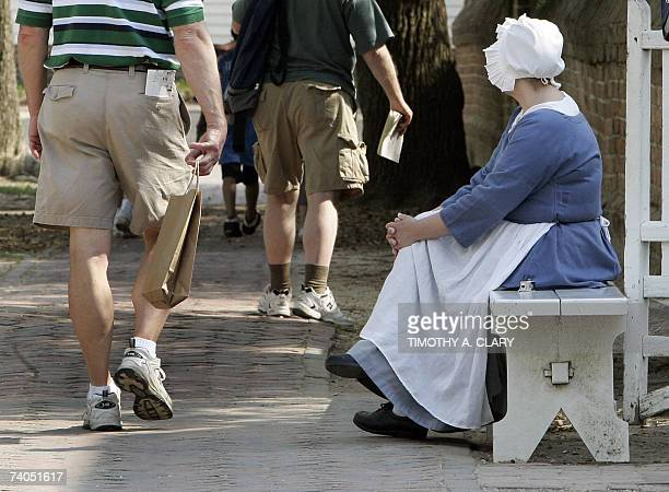 A worker dressed in colonialera watches tourist in colonial Williamsburg Virginia 02 May 2007 as the city prepares for a visit from Queen Elizabeth...