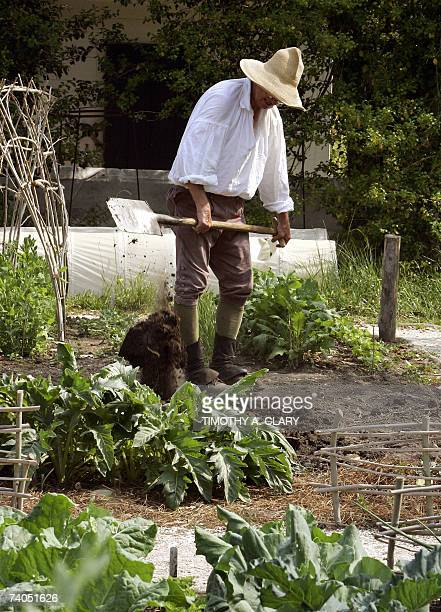 A worker dressed in colonialera works on a garden in colonial Williamsburg Virginia 02 May 2007 as the city prepares for a visit from Queen Elizabeth...