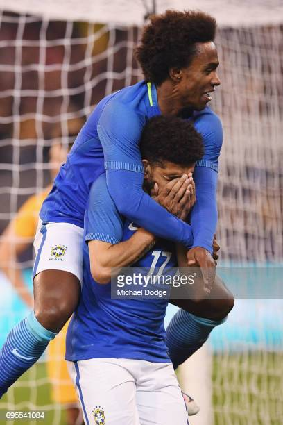 Willian jumps on top of Taison Freda of Brazil who celebrates a goal during the Brasil Global Tour match between Australian Socceroos and Brazil at...