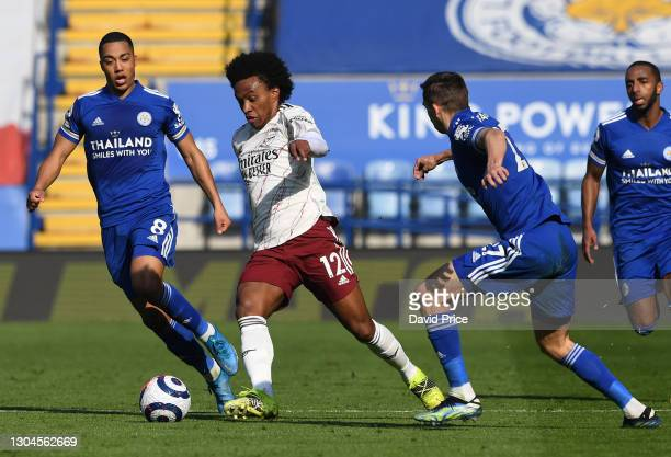 Willian of Arsenal takes on Youri Tielemans and Timothy Castagne of Leicester during the Premier League match between Leicester City and Arsenal at...