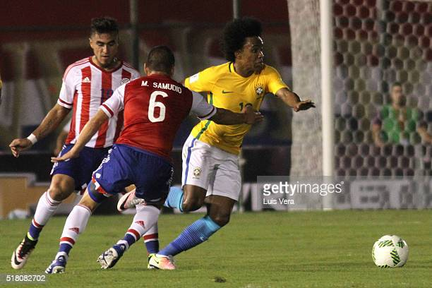Willian of Brazil drives the ball as Miguel Samudio and Dario Lezcano of Paraguay defend during a match between Paraguay and Brazil as part of FIFA...
