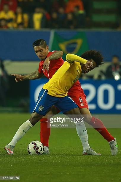 Willian of Brazil fights for the ball with Juan Vargas of Peru during the 2015 Copa America Chile Group C match between Brazil and Peru at Municipal...
