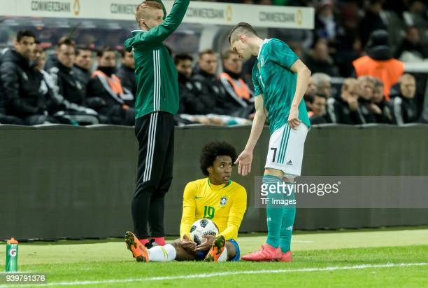 Willian of Brazil on the ground as Julian Draxler of Germany assists him during the international friendly match between Germany and Brazil at...