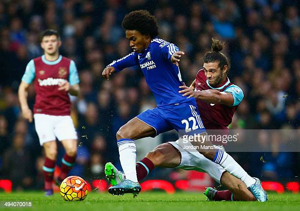 Willian of Chelsea and Andy Carroll of West Ham United compete for the ball during the Barclays Premier League match between West Ham United and...