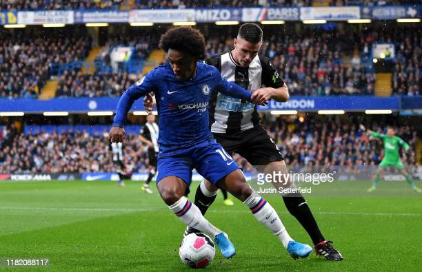 Willian of Chelsea and Ciaran Clark of Newcastle United during the Premier League match between Chelsea FC and Newcastle United at Stamford Bridge on...