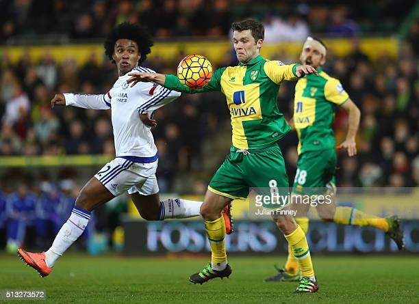Willian of Chelsea and Jonny Howson of Norwich challenge for the ball during the Barclays Premier League match between Norwich City and Chelsea at...