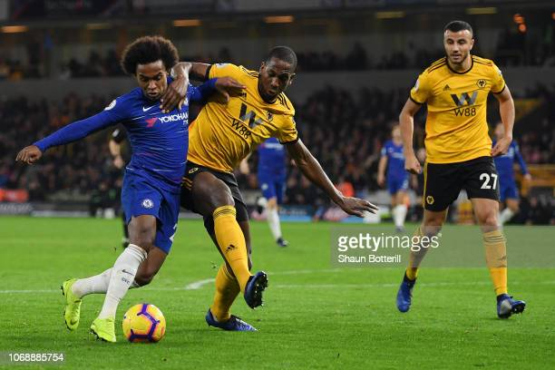 Willian of Chelsea battles for possession with Willy Boly of Wolverhampton Wanderers during the Premier League match between Wolverhampton Wanderers...