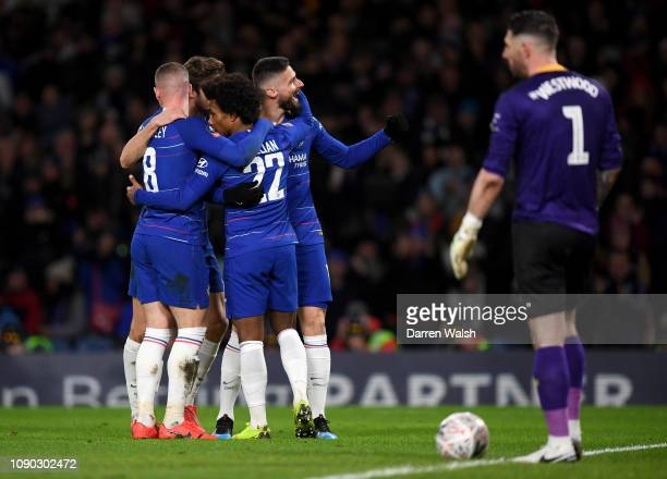 Willian of Chelsea celebrates after scoring his team's third goal with his team mates as Keiren Westwood of Sheffield Wednesday looks dejected during...