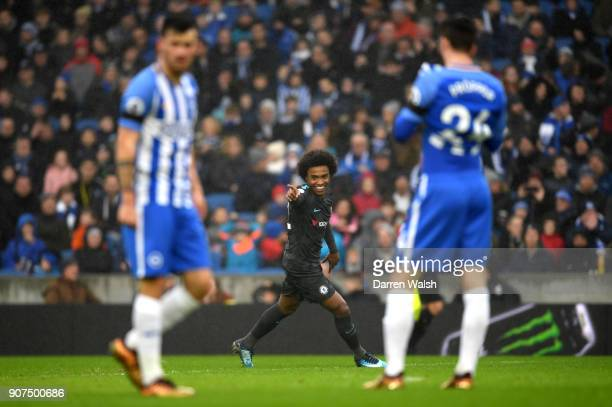 Willian of Chelsea celebrates as he scores their second goal as Brighton players look dejected during the Premier League match between Brighton and...
