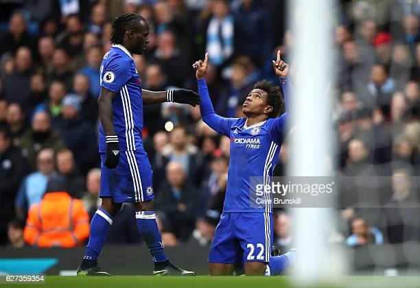 Willian of Chelsea celebrates scoring his team's second goal with his team mate Victor Moses during the Premier League match between Manchester City...