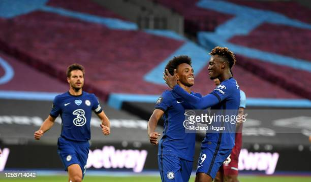 Willian of Chelsea celebrates with teammate Tammy Abraham after scoring his team's first goal from a penalty during the Premier League match between...