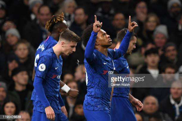Willian of Chelsea celebrates with teammates after scoring his team's first goal during the Premier League match between Tottenham Hotspur and...