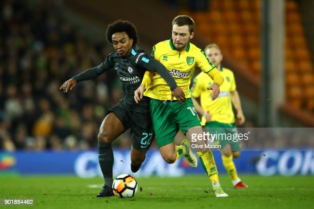 Willian of Chelsea challenges Tom Trybull of Norwich City during the Emirates FA Cup Third Round match between Norwich City and Chelsea at Carrow...