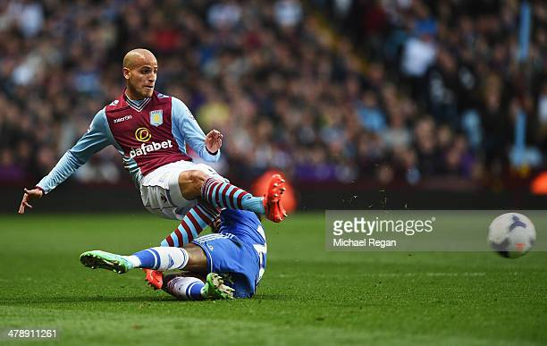 Willian of Chelsea fouls Karim El Ahmadi of Aston Villa and is booked during the Barclays Premier League match between Aston Villa and Chelsea at...
