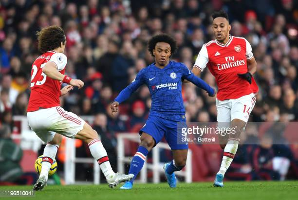 Willian of Chelsea goes past David Luiz of Arsenal under pressure from PierreEmerick Aubameyang of Arsenal during the Premier League match between...