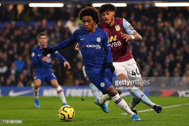 Willian of Chelsea holds off Tyrone Mings of Aston Villa during the Premier League match between Chelsea FC and Aston Villa at Stamford Bridge on...