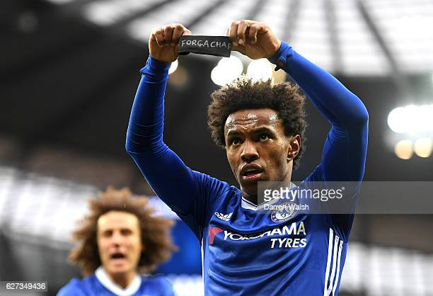 Willian of Chelsea holds up the black armband to commemorate the victims of the plane crash involving the Brazilian club Chapecoense after scoring...