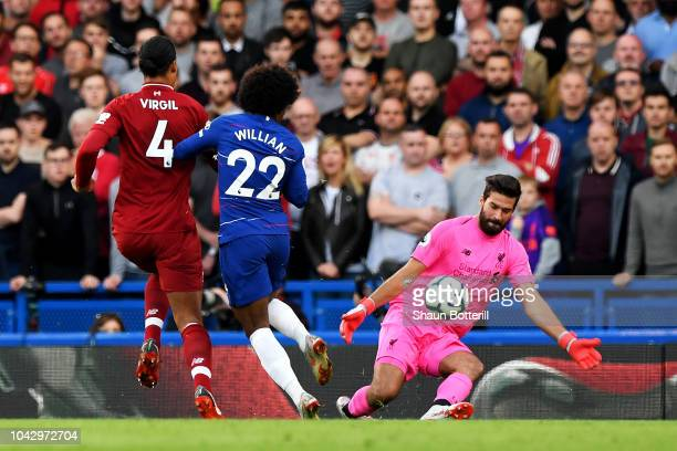 Willian of Chelsea is blocked by Alisson and Virgil van Dijk of Liverpool during the Premier League match between Chelsea FC and Liverpool FC at...