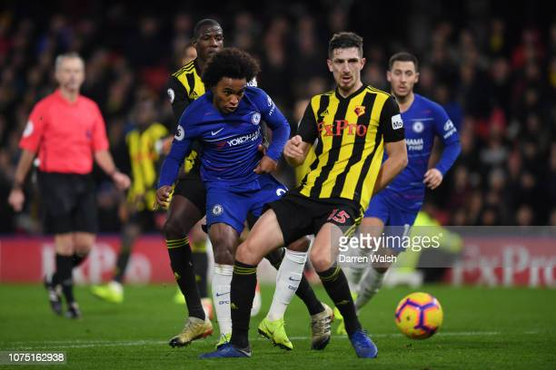 Willian of Chelsea is challanged by Craig Cathcart of Watford during the Premier League match between Watford FC and Chelsea FC at Vicarage Road on...