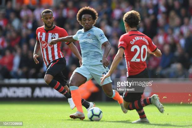 Willian of Chelsea is challenged by Manolo Gabbiadini of Southampton during the Premier League match between Southampton FC and Chelsea FC at St...