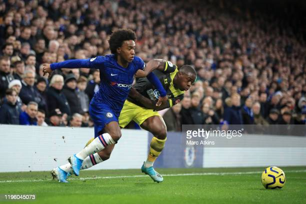 Willian of Chelsea is challenged by Michael Obafemi of Southampton during the Premier League match between Chelsea FC and Southampton FC at Stamford...