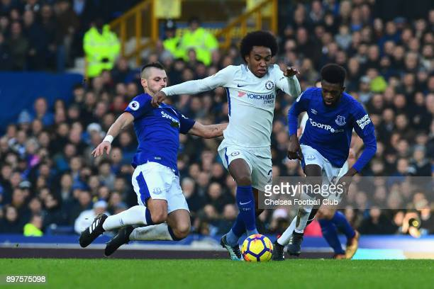 Willian of Chelsea is challenged by Morgan Schneiderlin of Everton during the Premier League match between Everton and Chelsea at Goodison Park on...
