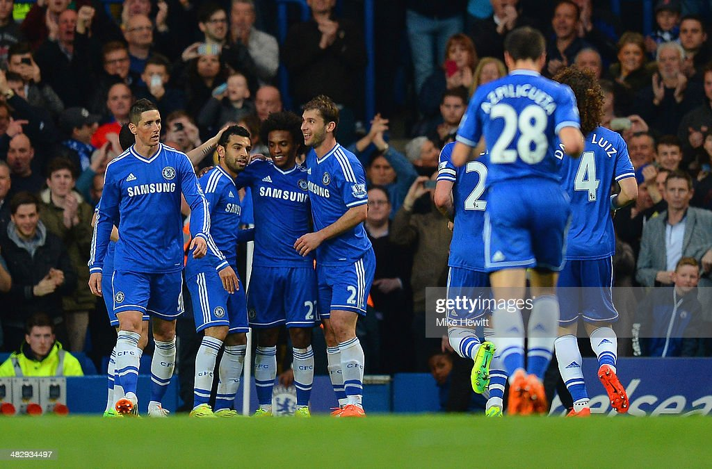 Willian of Chelsea is congratulated by Branislav Ivanovic and Mohamed Salah of Chelsea on scoring their third goal during the Barclays Premier League match between Chelsea and Stoke City at Stamford Bridge on April 5, 2014 in London, England.