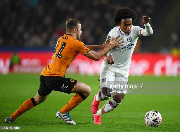Willian of Chelsea is held by Herbie Kane of Hull City during the FA Cup Fourth Round match between Hull City FC and Chelsea FC at KCOM Stadium on...